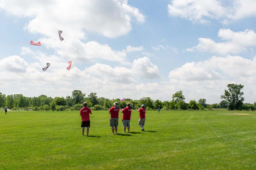 Five people in red t-shirts flying four coordinated red and gray kites