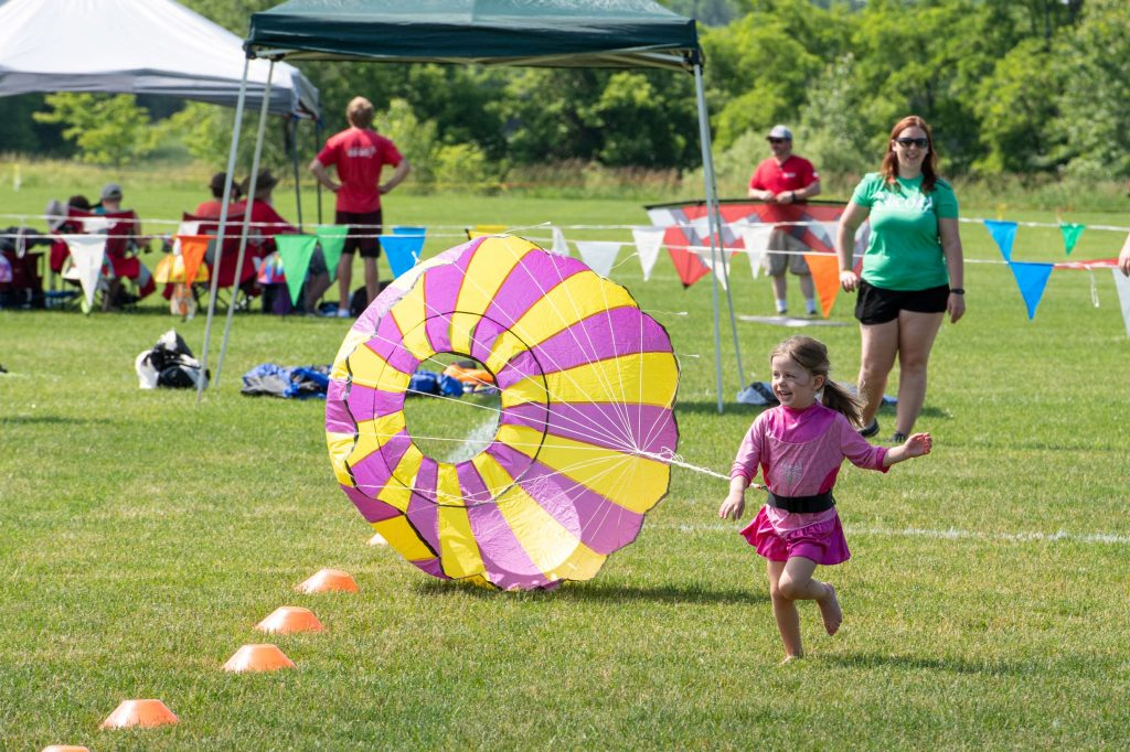 Girl in pink running with yellow and pink parachute