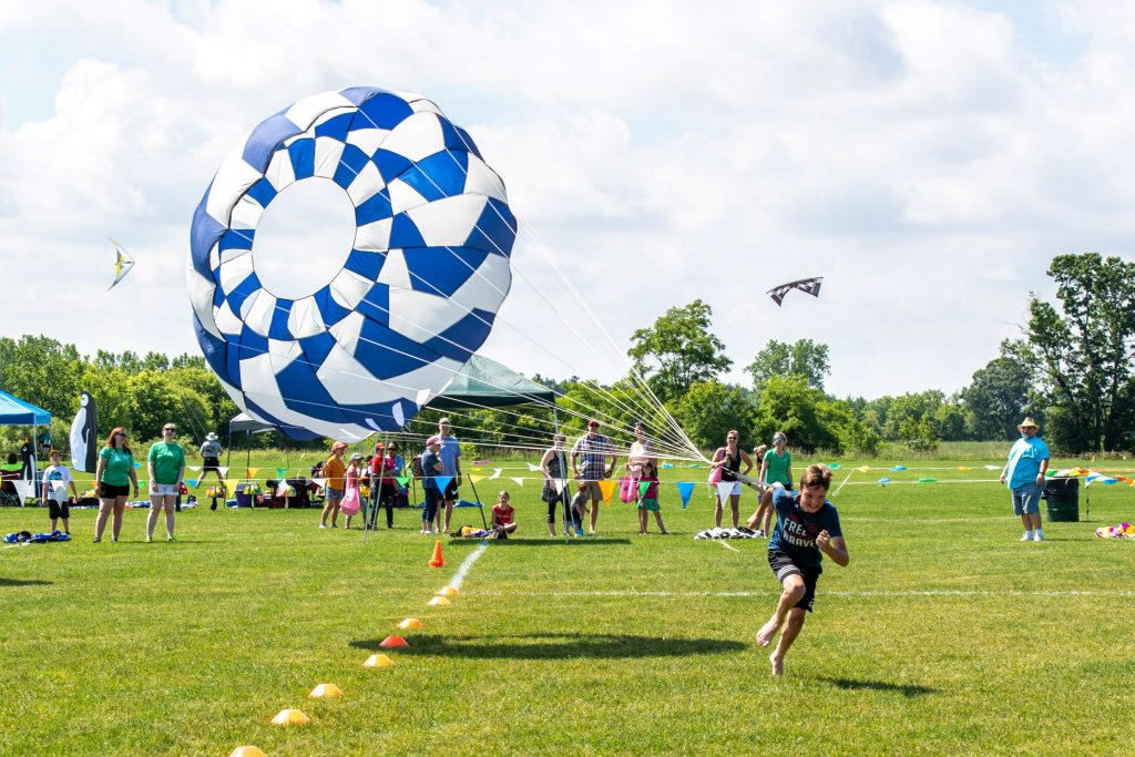 Boy running across green field with blue parachute
