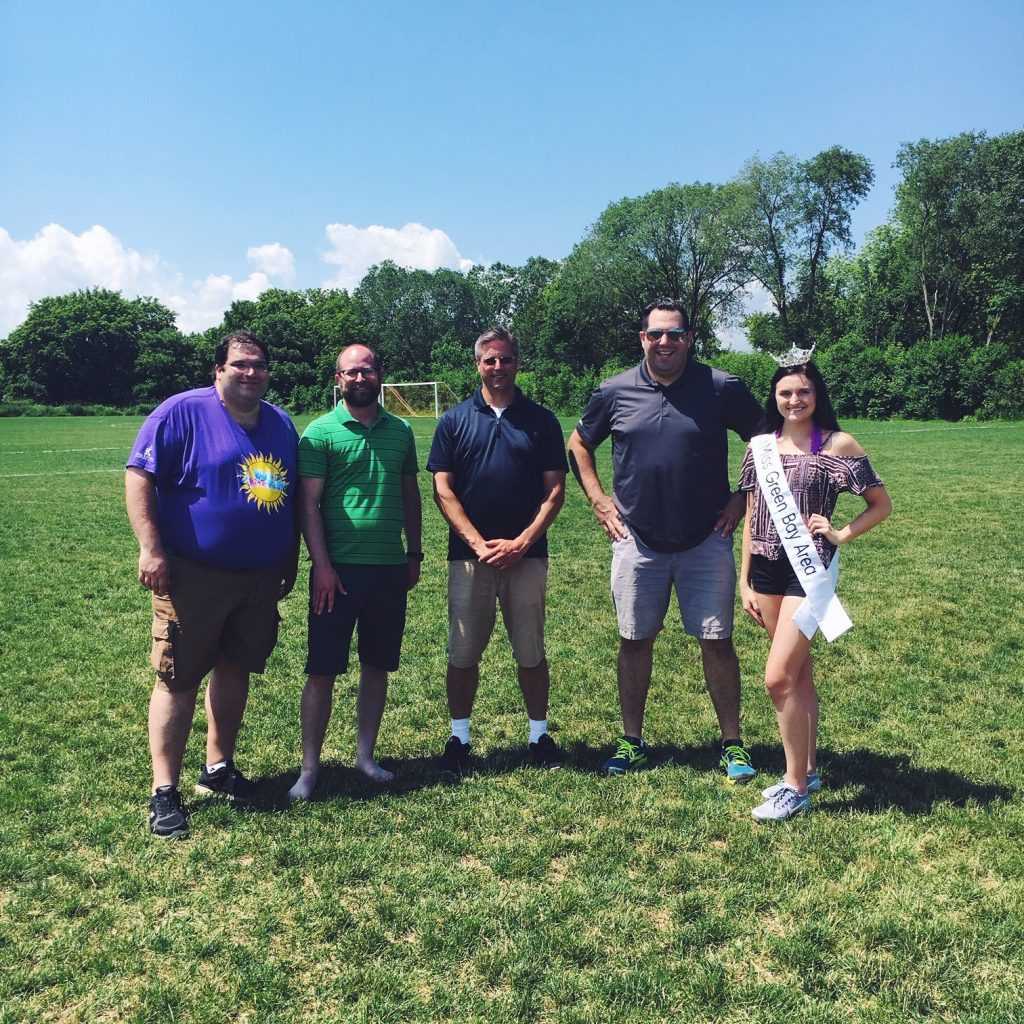Four white people standing in a green field in the day